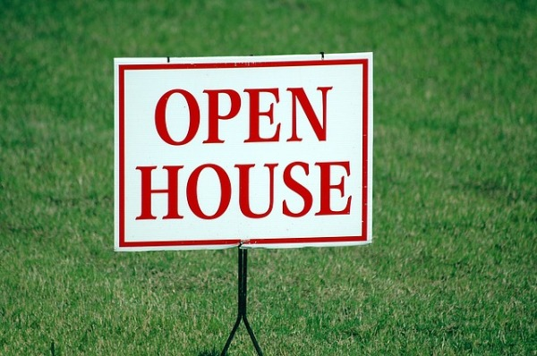 Open house sign with green grass in the background