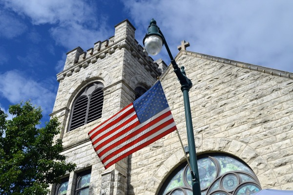 An American flag flies on a lamp post outside of an old church